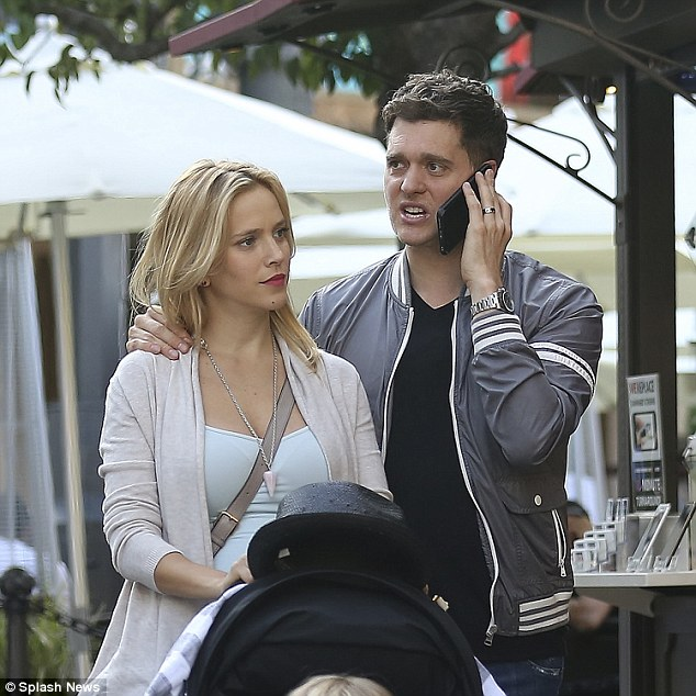 Multi-tasking: The crooner - who turns 40 next week - seemed caught up on a phone call, as he walked with his pregnant wife