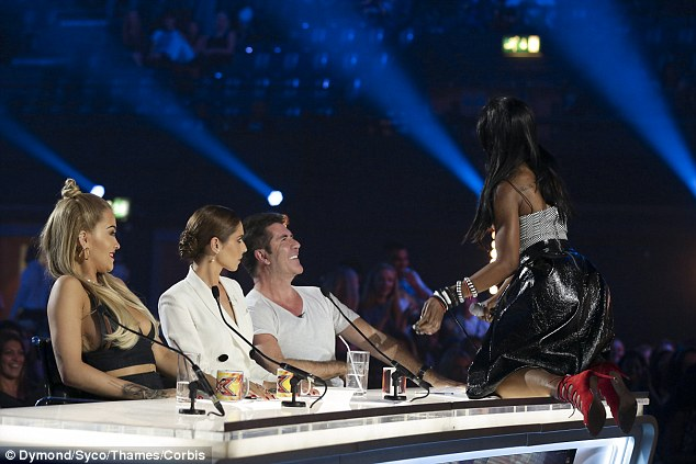 Shaking it: The singer offered Simon a shimmy of her chest as she danced on the table