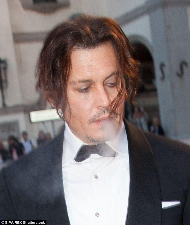Don't mind me: Johnny took a puff off his cigar on the red carpet, strands of his hair falling onto his face