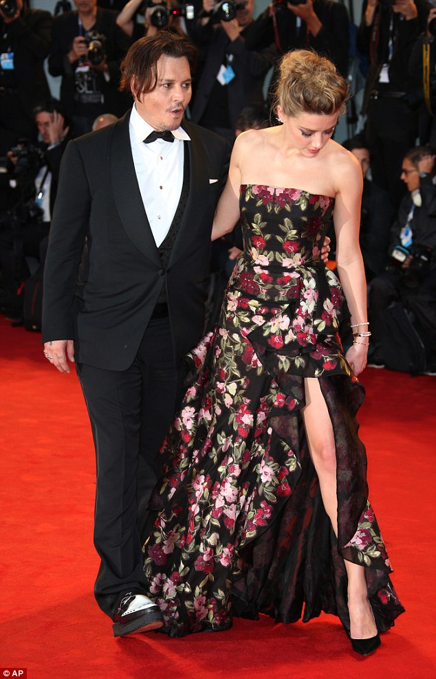 Everything's in check: Amber admired her floral gown, that she teamed with a pair of black stilettos