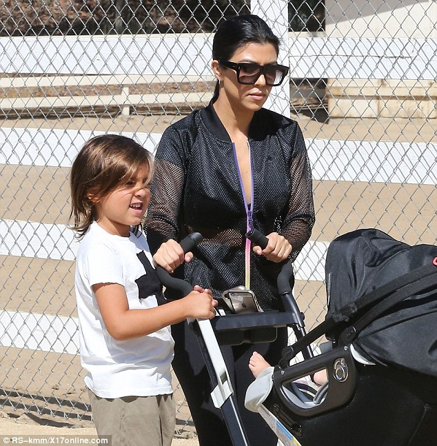 Let's go, mom: Mason was in for the long haul while Kourtney kept a shaded eye on her nine-month-old boy Reign beneath the hood of the stroller