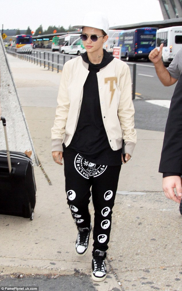 Hot stepper: Ruby teamed the low drop trousers with matching black and white Converse trainers, while she continued a monochrome theme with a simple black hoody and a cream letterman jacket