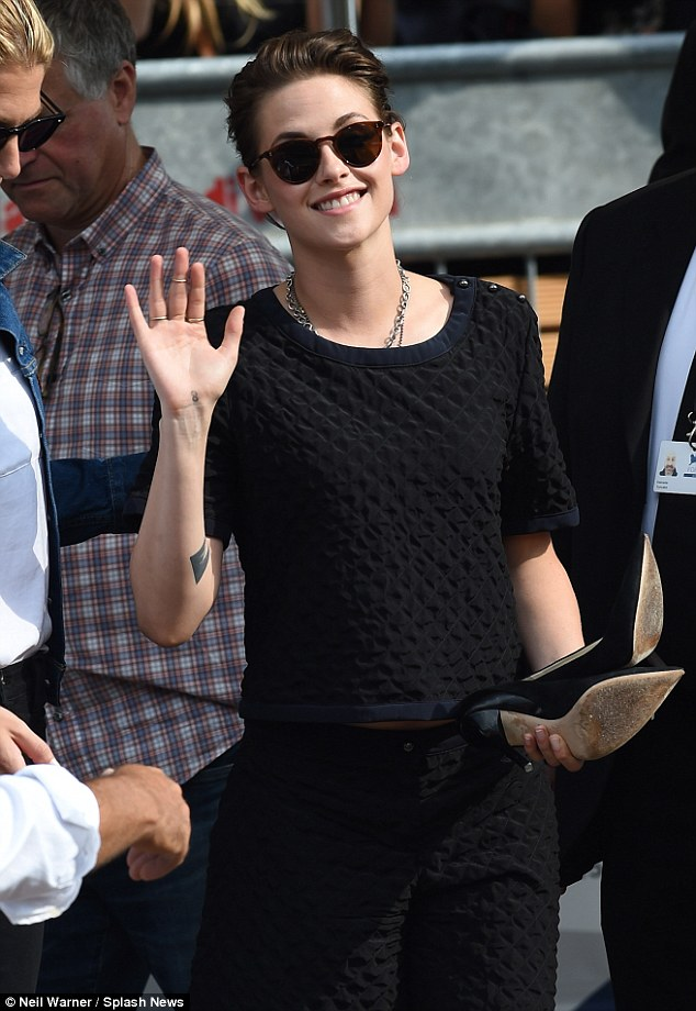 Happy chappy: Kristen waved to fans as she clutched her shoes close to her