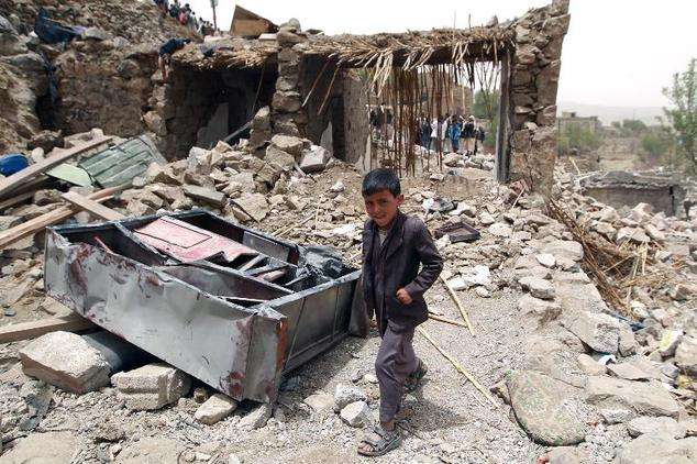 A Yemeni boy walks past the rubble of destroyed houses in the village of Bani Matar, 70 kilometers (43 miles) west of the capital Sanaa, on April 4, 2015, a ...