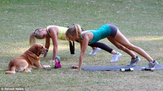 Pet pal: Kimberley was joined for her personal training session by her pet labrador, Nismo, who looked unimpressed as the pair did a plank on their mats, surrounded by free weights and kettlebells