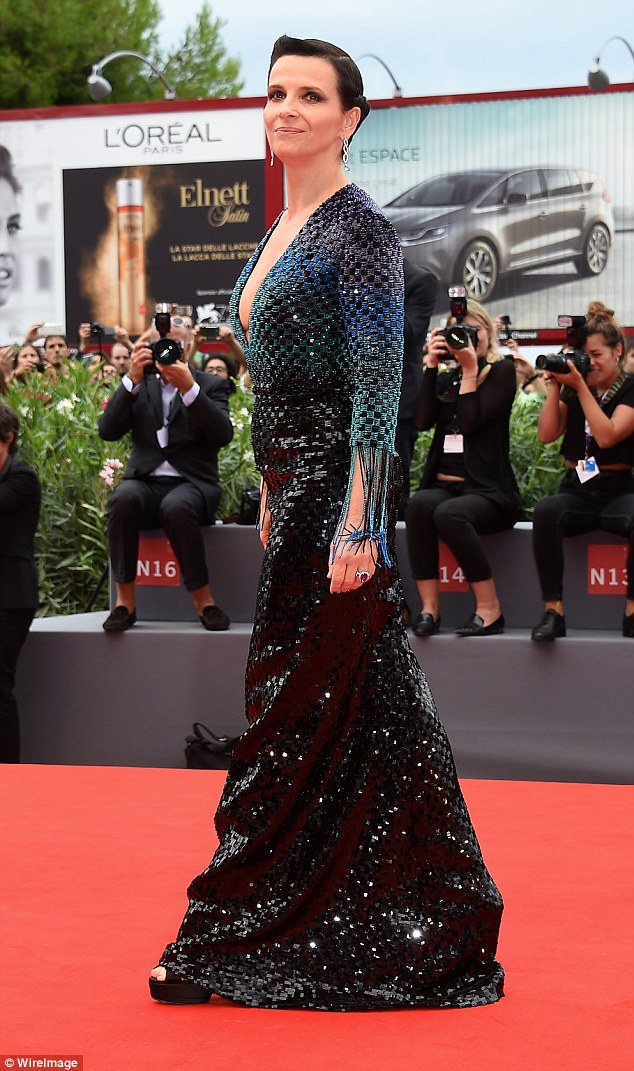 Easy does it: Flashing a glimpse of her black sky scrapper heels that she kept hidden beneath her gown, Juliette minded her step as she made her way through arrivals in the fishtail number