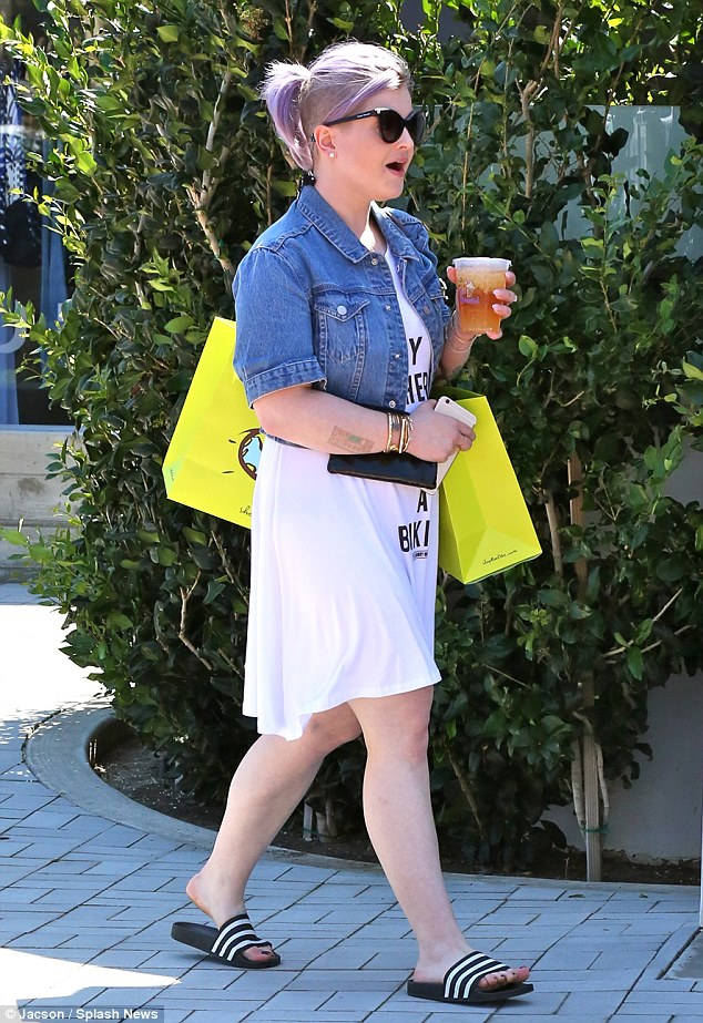 Shopping spree: Kelly balanced two large shopping bags as she carried a refreshing drink