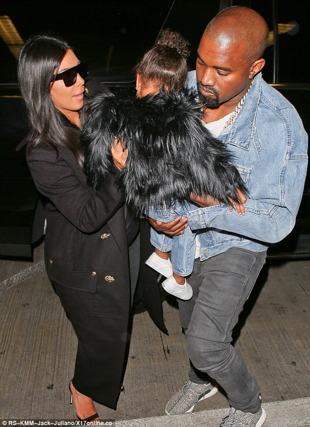 Precious cargo: Kanye carefully handed Nori into his wife's arms as they exited a car