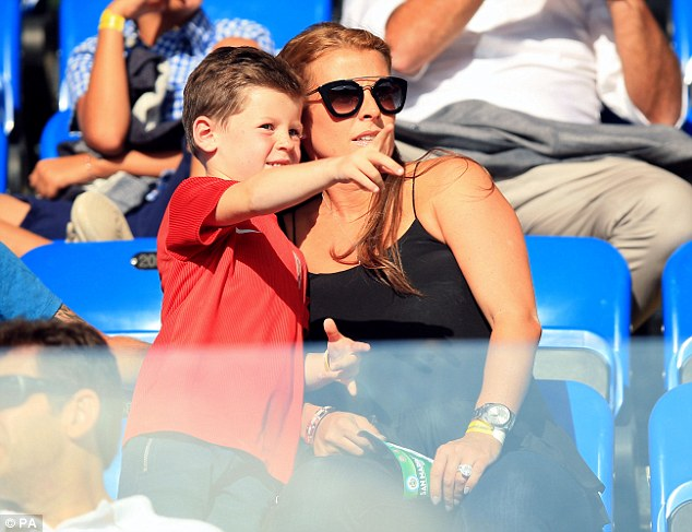 Cute twosome: Coleen Rooney was seen cosying up to cute son Kai as they watched Wayne play football in San Maino on Saturday