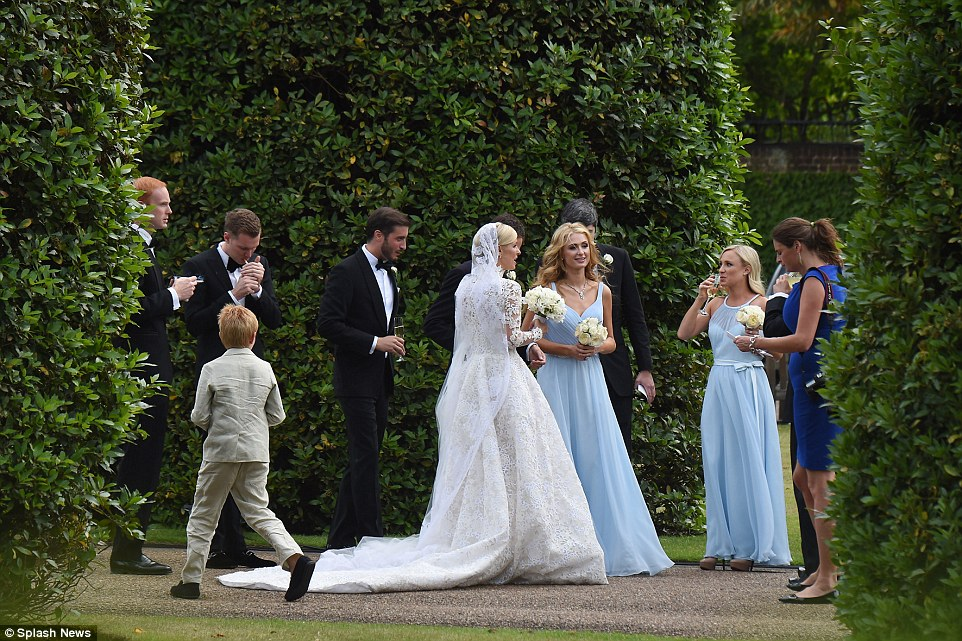 Wedding party: Nicky and Paris' brother Barron is seen lighting a cigarette at Kensington Palace enjoy cocktails and cigarettes, left, on the special day