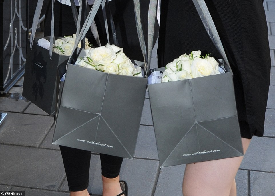 Beautiful: The helpers carried boxes of bridal bouquets made from pretty cream roses