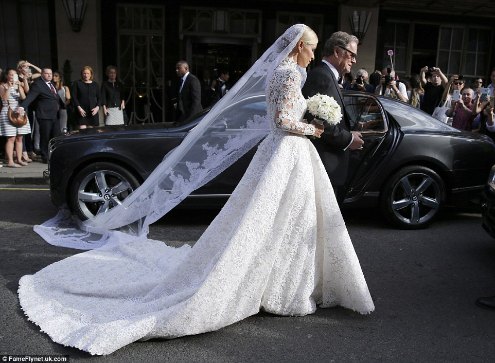 Newly wedged: The bride's lace veil and the train of the £50,000 dress gets caught underneath the wheel of the bridal car