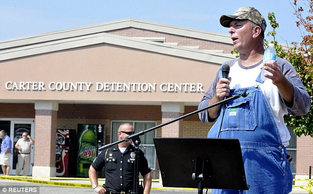 Davis' husband, Joe (pictured as he speaks to supporters of his wife outside the detention center on Saturday), told Daily Mail Online that she was 'holding up real good' and was prepared to sit in prison for months after being jailed for refusing to grant marriage licenses to gay couples