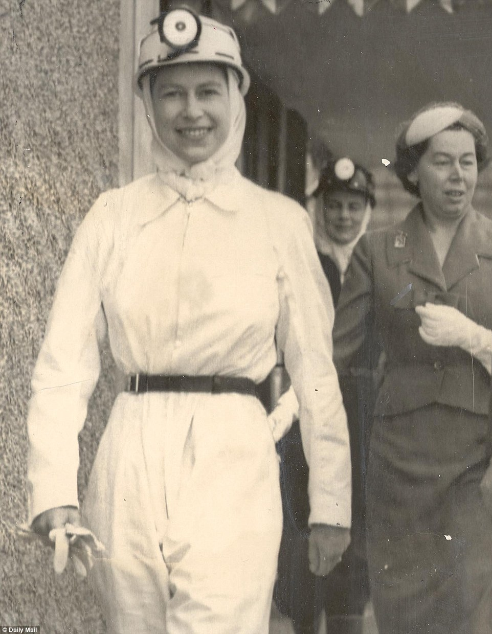 1958: Dressed in white togs, black gumboots and a miner's helmet, the Queen prepares to go down Rothes Colliery during a visit to Fife, Scotland