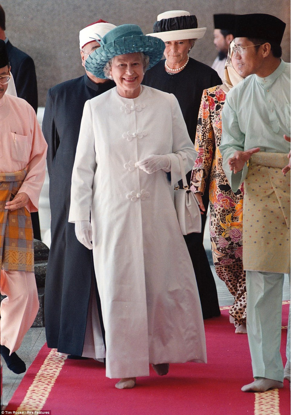 1998: Minus her shoes, the Queen attends a religious shrine dressed in an elegant white coat while on a state visit to Malaysia