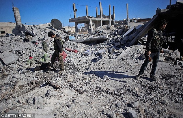 Two men asses the damage in Kobane. As well as the civil war, the town has been penetrated by Islamic State fighters who detonated suicide bombs