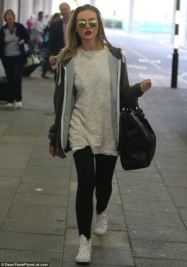 Head held high: Appearing slightly downcast after her long-haul flight, the 22-year-old cut a relatively simple, yet, perfectly stylish figure in a slouchy white T-shirt and a dark hoodie