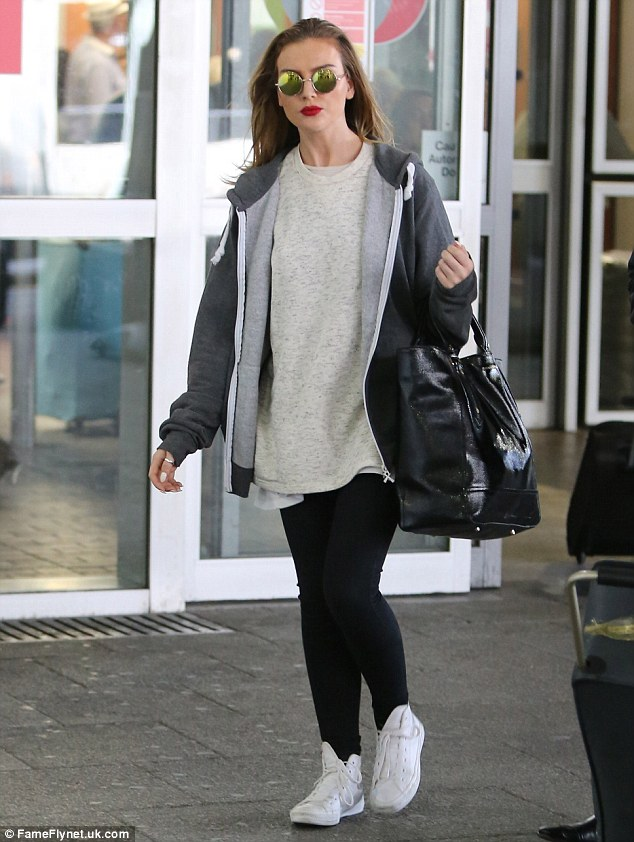 Back on home turf: Perrie Edwards arrived back in the UK with her Little Mix bandmates on Sunday afternoon after a mammoth promotional tour in the States