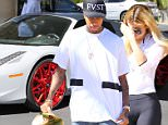 Tyga, Kylie Jenner gassing up her new Lamborghini wearing Yeezy Nikes and a new tattoo that reads, RAP STAR.  September 6, 2015