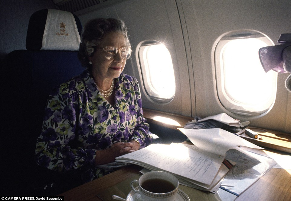 Heading home: The Queen travelling on a plane from the Royal Flight following a visit to Belfast in June 1991