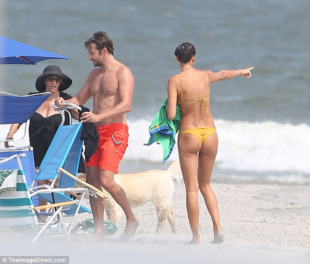 Setting up: Cooper unfolded a beach chair and chatted with his mother as something else caught Shayk's eye