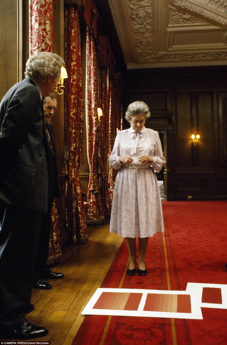 Difficult choice: The Queen pictured furrowing her brow while choosing curtain fabric for Holyroodhouse