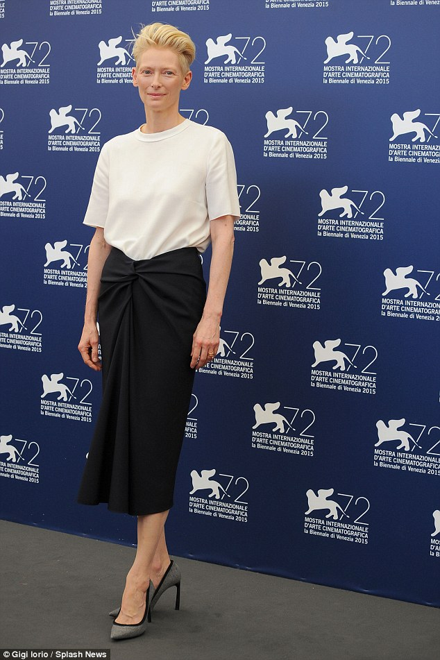 All change: Earlier in the day at the film's photo call, Tilda rocked a classic and simple outfit, comprised of a t-shirt and navy wrapover-fronted skirt