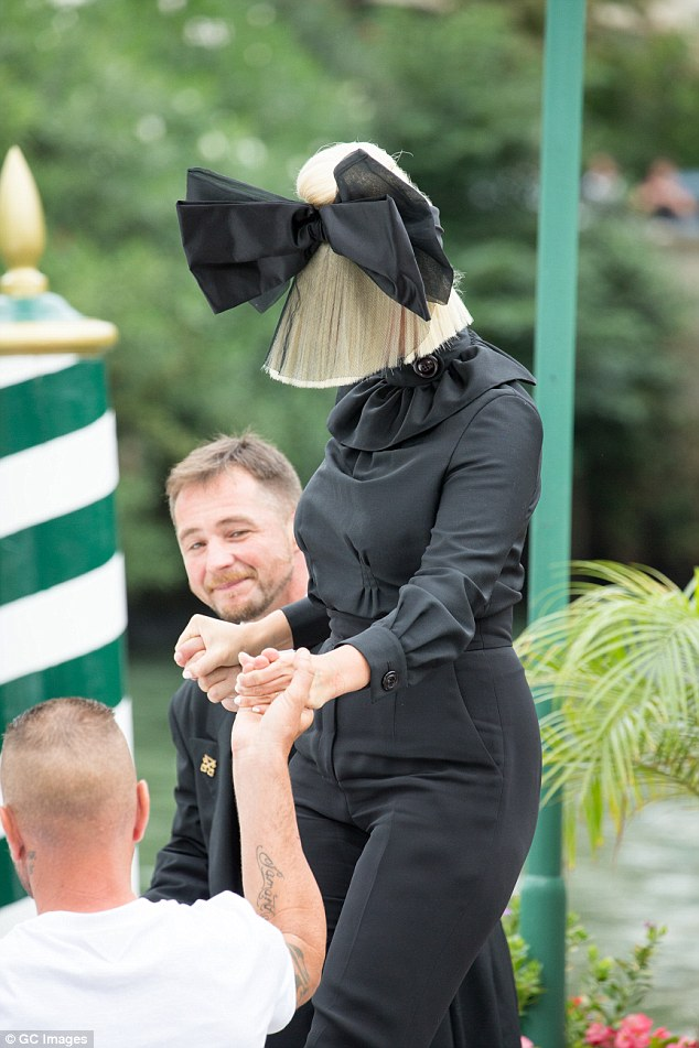 A helping hand:The style conscious artist teamed the elaborate headgear with a chic all black ensemble for a dramatic look that had overtones of the macabre