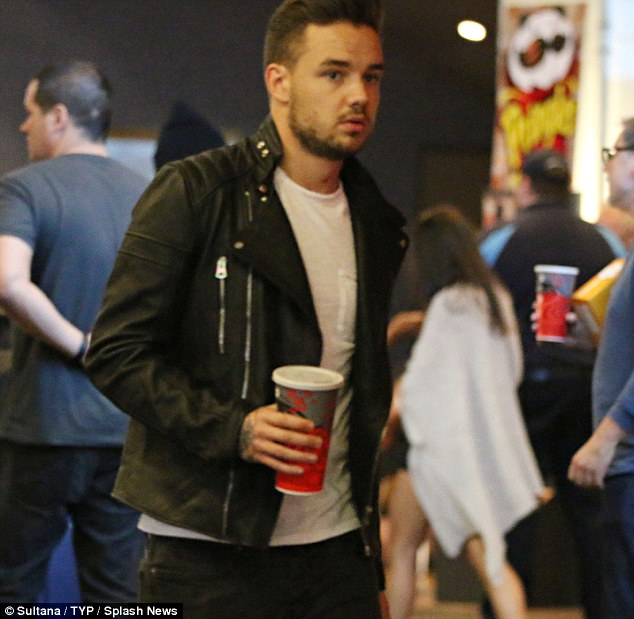 Looking good; Wearing a white T-shirt with black, skinny jeans and a leather jacket the chart-topper looked typically handsome as he clutched a large soft drink and some popcorn