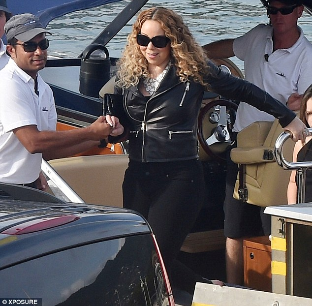 Steady as she goes: Mariah, 45, was given a helping hand as she stepped off the boat