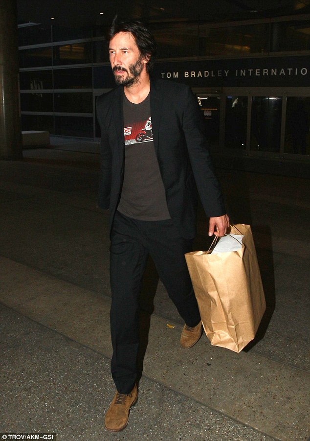 Sleek: Keanu Reeves looked stylish in a black suit as he arrived at LAX on Sunday following a visit to France to attend theDeauville American Film Festival