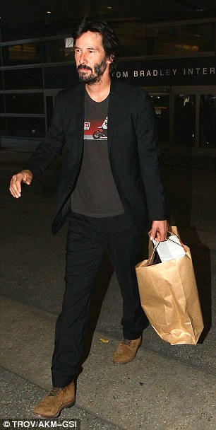 Classic: The Speed star sported his favorite pair ofdistressed suede boots as he arrived at the Los Angeles airport