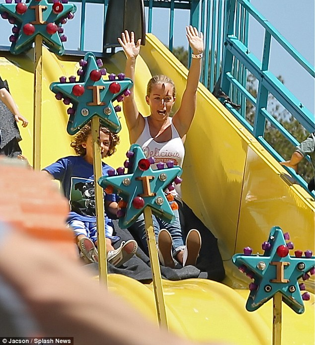 Like this: Kendra lifted her hands in the air as the pair zoomed down the bright yellow slide