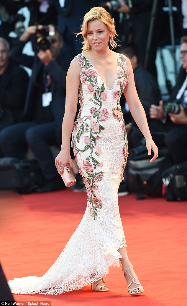 Beautiful: Elizabeth Banks made an impression as she arrived at the premiere, cutting a fine figure in a white lace and floral dress with a deep plunging neckline