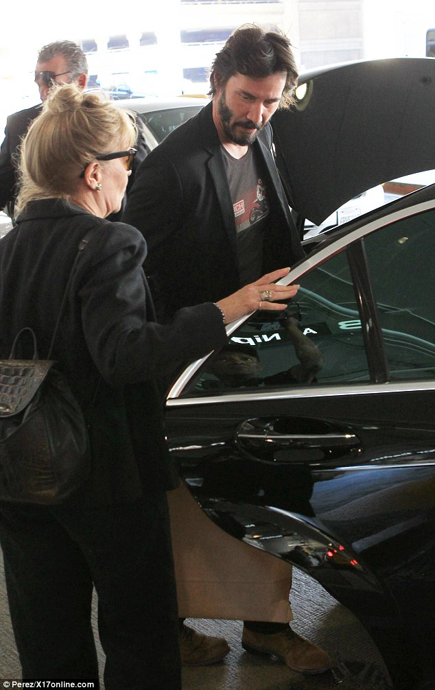 Helping hand: He was spotted chatting with a woman similarly dressed in all black as bags were loaded into his car