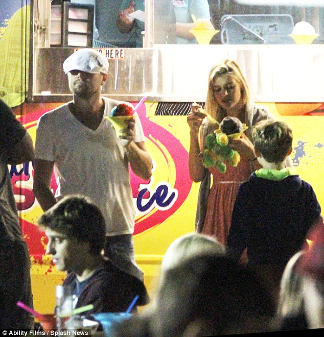 Tucking in: Leonardo DiCaprio took girlfriend Kelly Rohrbach to Malibu Fair on Sunday evening and snacked on snow cones together