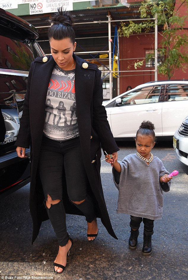 Treats: North held a pink toy and lollipops as mom Kim held on tight to her young daughter