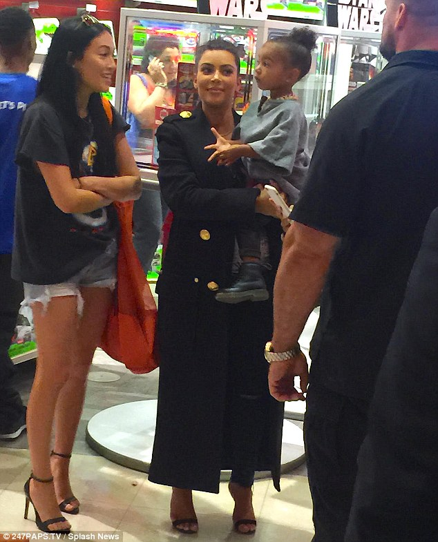 Decisions, decisions: North weighs up her options as she rests in Kim's arms at the Times Square Toys 'R' Us