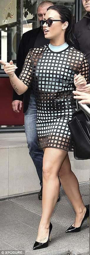 Stepping out in style: The singer wore an edgy cage outfit over a white mini and crop top