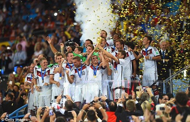 On top of the world: Germany celebrate as they lift the iconic trophy at the Maracana