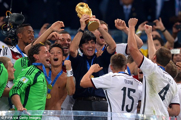 The boss: Germany coach Joachim Low (centre) lifts the World Cup as his players celebrate around him