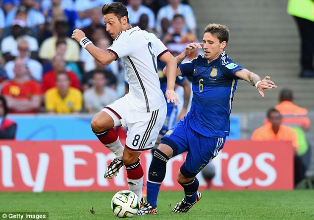 Shadow play: Mesut Ozil tries to evade Argentina midfielder Biglia in the early stages