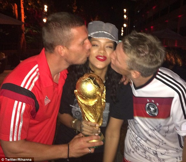 Stuck in the middle with you: Rihanna holds the World Cup while Lucas Podolski and Bastian Schweinsteiger kiss her
