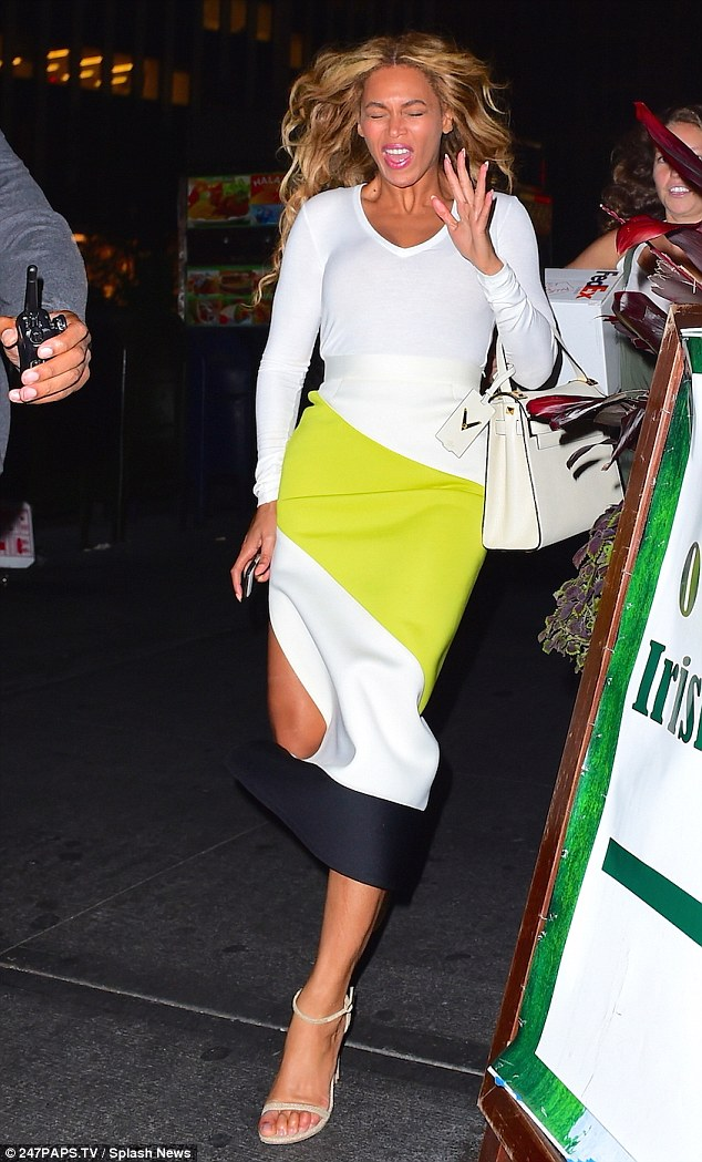 End of summer chic: The singer, 34, wore a figure-hugging dress that had a broad green stripe and an uneven black hem and went bare-legged in strappy sandals