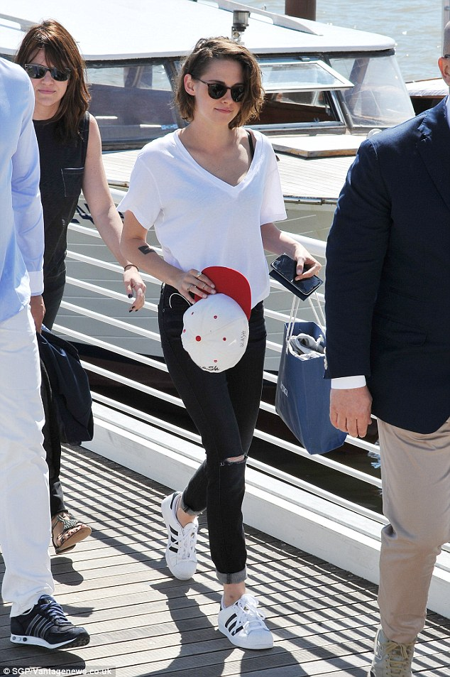 Casual: She showed off her slim figure in skinny jeans, with on-trend ripped knees, which she teamed with a loose fitting V-neck t-shirt that flashed her black bra underneath