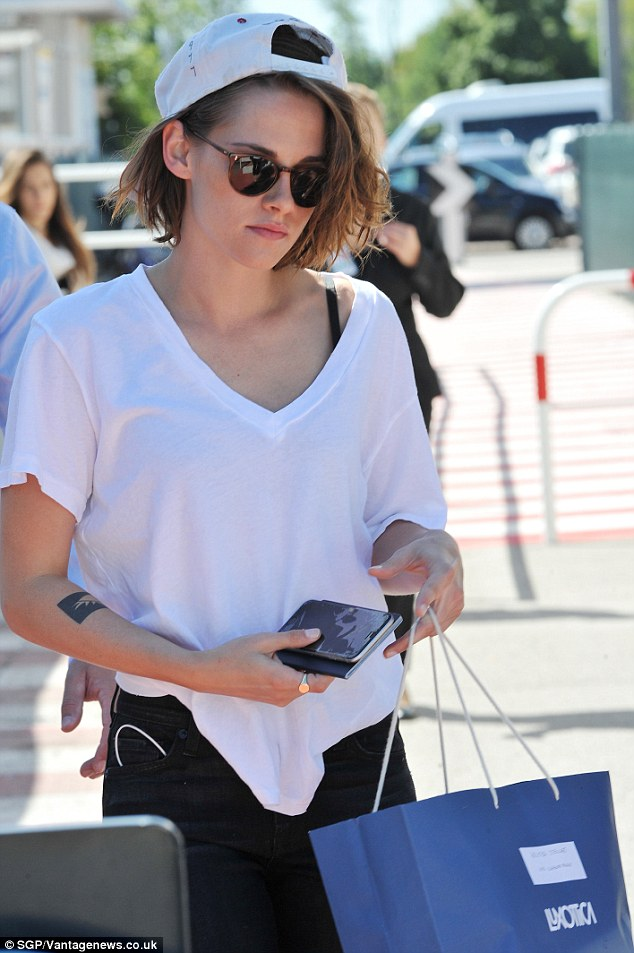 Sunny days: The star covered her tousled brunette locks briefly with a baseball cap and protected her eyes  in dark glasses