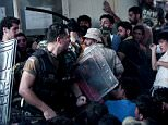 A picture taken on September 3, 2015 shows special forces of the Hellenic Coast Guard hitting migrants with batons who are waiting to be registered by police in the port of Mytilene, on the Greek Aegean island of Lesbos. More than 230,000 refugees and migrants have arrived in Greece by sea this year, a huge rise from 17,500 in the same period in 2014, deputy shipping minister Nikos Zois said on September 3. AFP PHOTO / ANGELOS TZORTZINISANGELOS TZORTZINIS/AFP/Getty Images