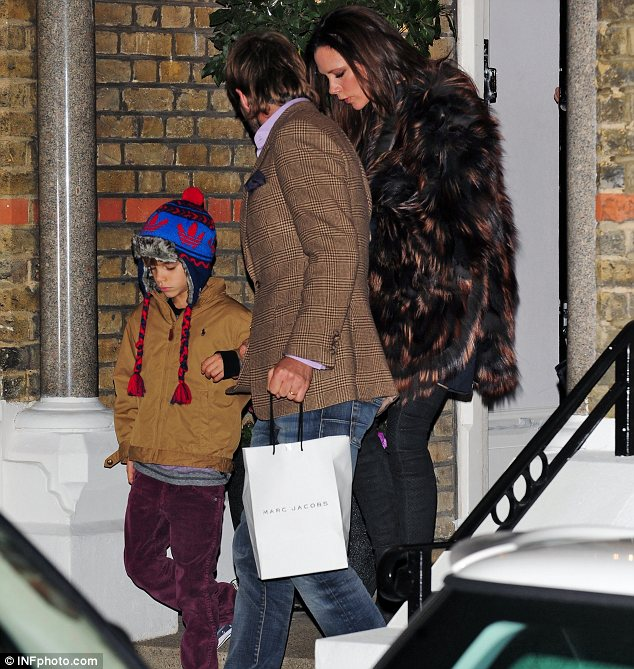 Dressing up: Victoria opted for a black and orange fur jacket while David opted for an English heritage look complete with a brown cravat in his top pocket. Cruz rugged up against the elements with a Christmas hat
