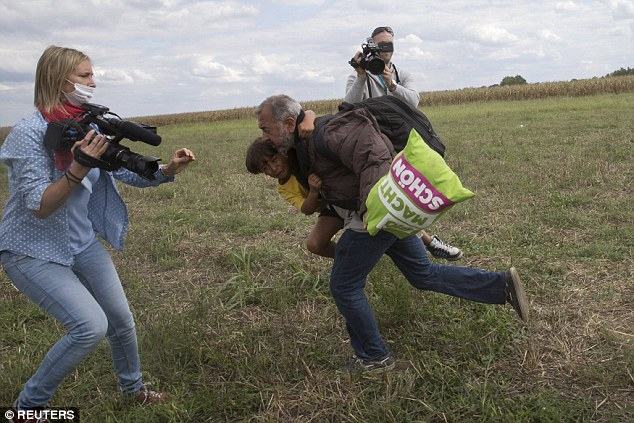 Laszlo, working for N1TV, was filming the crowds of Syrian refugees as they ran across a field from Roszke camp. Above, the man who gets tripped over is pictured moments before carrying a crying child