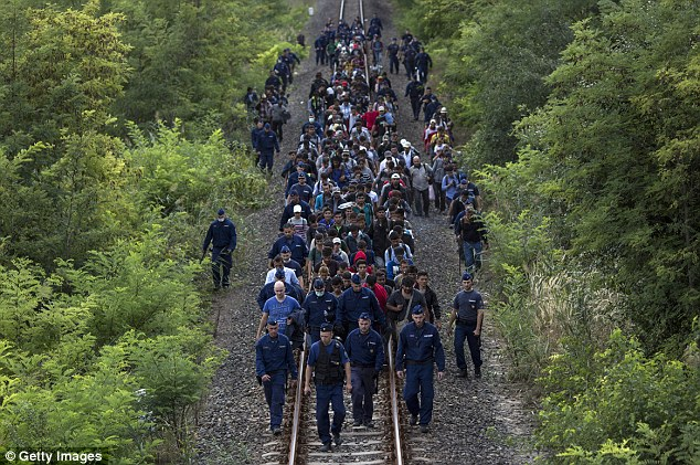 Hundreds of migrants guarded by police were forced to walk several miles along rail tracks towards the town of Szeged after breaking away from the collection point